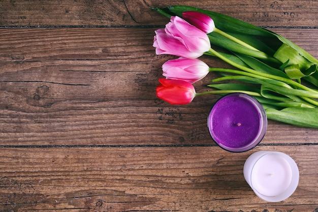 Różowe kwiaty tulipana i dwa cendele na rustykalnym stole do 8 marca, międzynarodowy dzień kobiet, urodziny, walentynki lub dzień matki - widok z góry