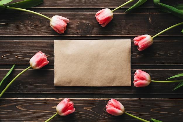 Różowe kwiaty tulipany z papierową kopertę pocztową na drewnianym stole