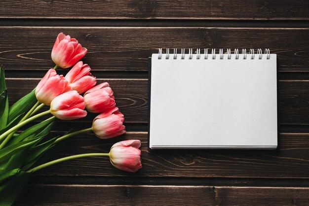 Różowe kwiaty tulipany z pustego notatnika na drewnianym stole dla karty z pozdrowieniami