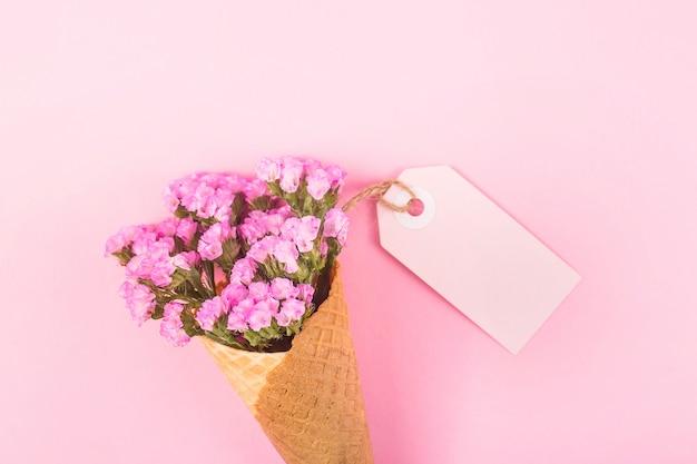 Różowe kwiaty w stożku lodów waflowych na jasnym tle obok pustej etykiety.