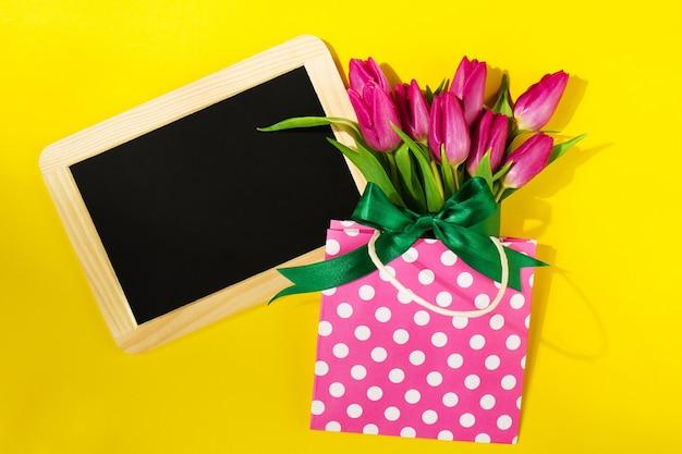 Różowe kwiaty w torbie z tablicy obok niego