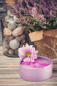 Różowe kwiaty wrzosu i fioletowe pudełko