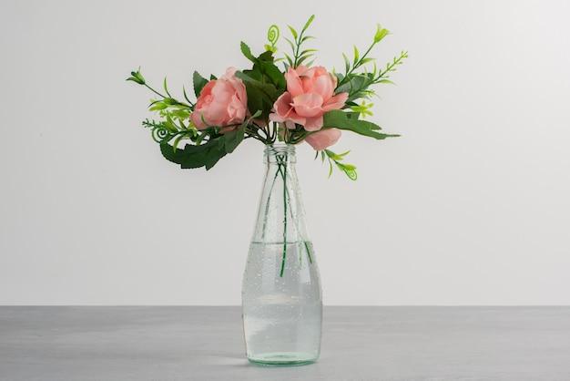Różowe kwiaty z zielonymi liśćmi w szklanym wazonie