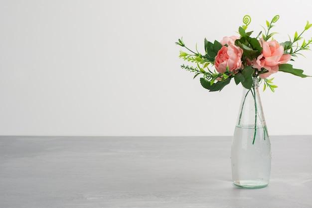 Różowe kwiaty z zielonymi liśćmi w szklanym wazonie.