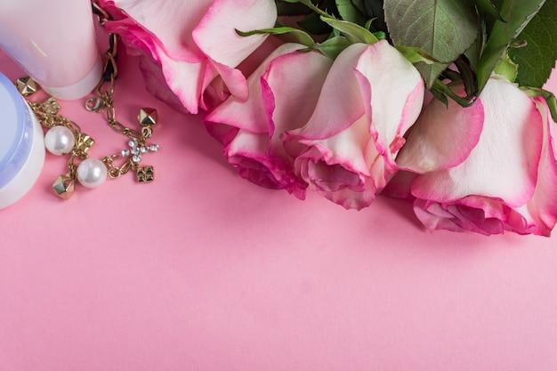 Różowe kwitnące róże i krem do twarzy na pastelowym różowym tle. romantyczna rama do pielęgnacji skóry. skopiuj miejsce