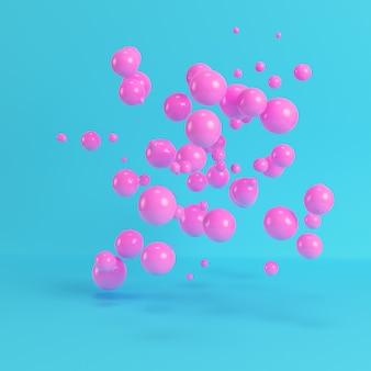 Różowe latające kule na jasnym niebieskim tle w pastelowych kolorach