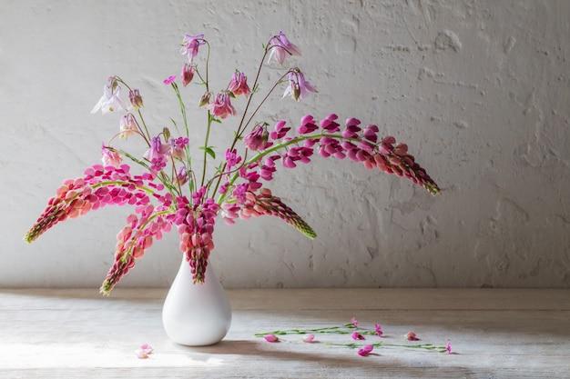 Różowe letnie kwiaty w białym wazonie na białym starym