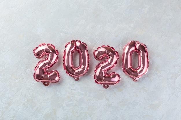 Różowe liczby 2020 na białym betonie