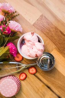 Różowe lody w misce w pobliżu miarka z kawałkami świeżych jagód i kwiatów