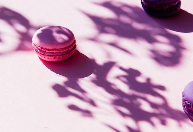 Różowe makaroniki i cień gałęzi na różowej powierzchni. powyżej widok