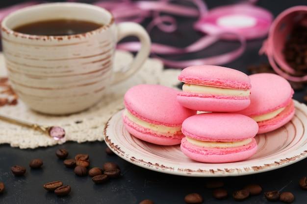 Różowe makaroniki i filiżanka kawy znajdują się na talerzu na ciemnym tle