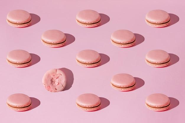 Różowe makaroniki z czekoladowym kremowym wzorem z twardymi cieniami na modnym różowym tle