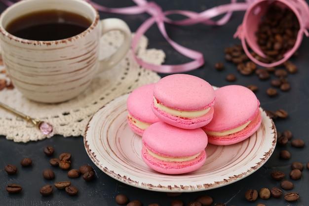 Różowe makaroniki znajdują się na talerzu na ciemnym tle