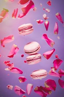 Różowe makrony i płatki róż latają w powietrzu na fioletowej ścianie