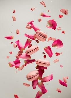 Różowe makrony i płatki róż latają w powietrzu na szarej powierzchni