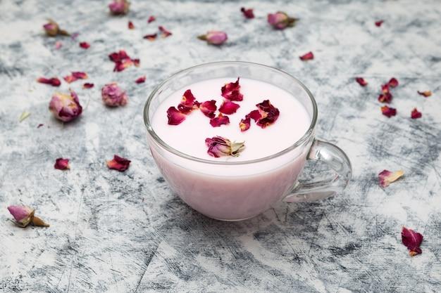 Różowe mleko księżycowe w przezroczystym kubku o północy relaksujący napój róże szare tło z teksturą