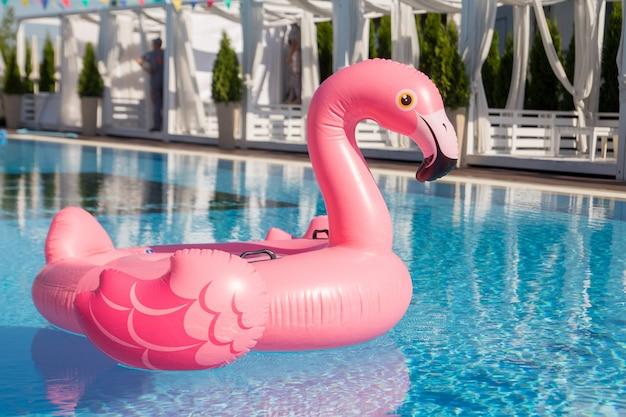 Różowe nadmuchiwane flamingi pływają w basenie