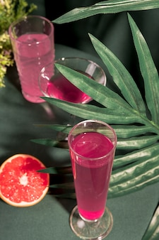 Różowe napoje o wysokim kącie obok grejpfruta