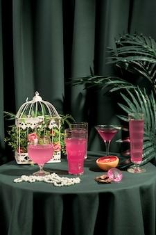 Różowe napoje obok modnych ozdób na stole