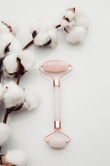 Różowe narzędzie do masażu gua sha. wałek z różowego kwarcu. domowa pielęgnacja skóry twarzy, terapia przeciwstarzeniowa i liftingująca. obraz pionowy