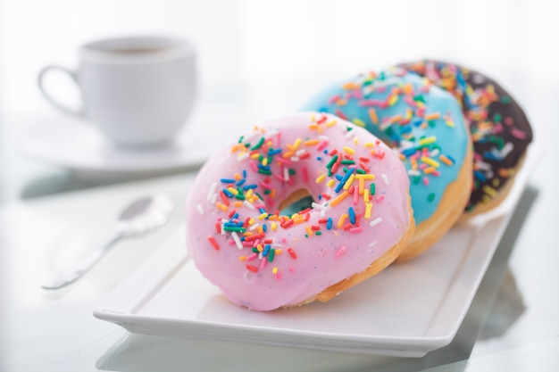 Różowe, niebieskie i czekoladowe posypki pączków na białym talerzu i filiżance kawy