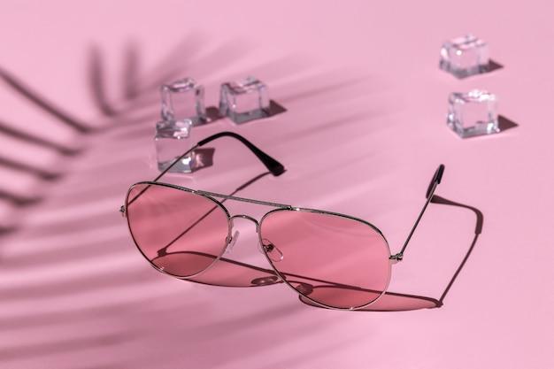 Różowe okulary przeciwsłoneczne i kostki lodu pod palmą