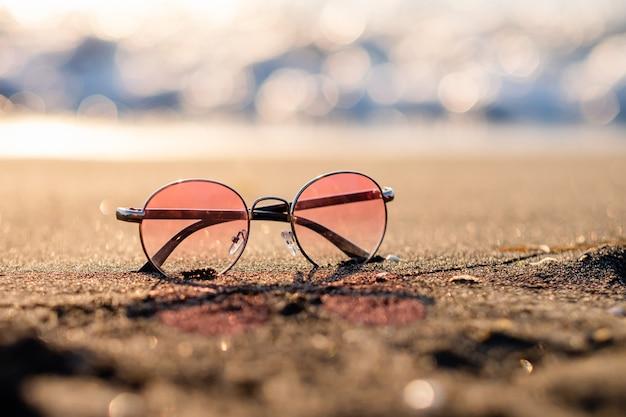Różowe okulary przeciwsłoneczne leżą na piaszczystej plaży na tle morza o zachodzie słońca. letnie wakacje, miejsce na tekst