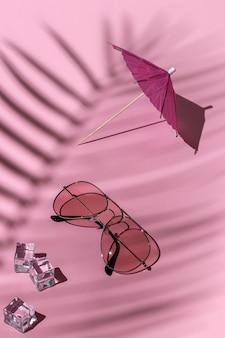Różowe okulary przeciwsłoneczne, parasol plażowy i kostki lodu pod palmą