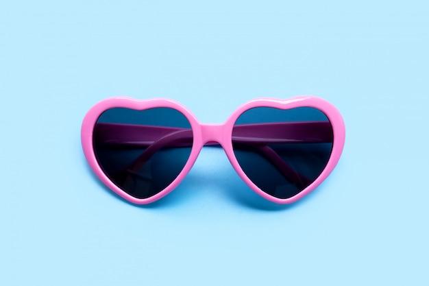 Różowe okulary przeciwsłoneczne w kształcie serca na niebieskiej powierzchni. widok z góry