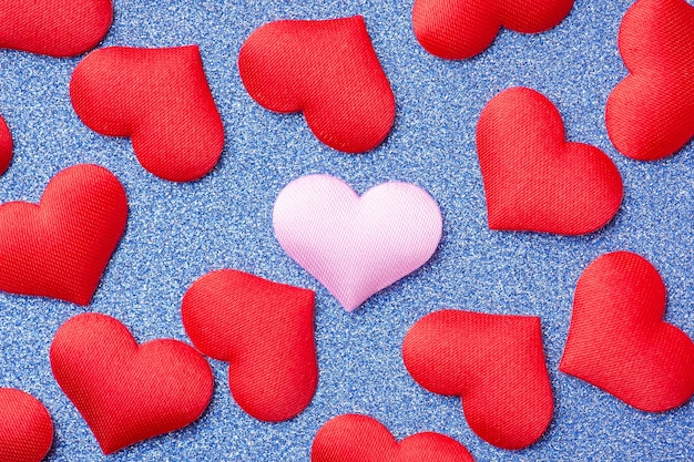 Różowe ozdobne serce w środku wielu czerwonych serc na niebieskim tle musujące