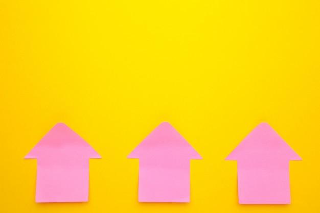 Różowe papierowe karteczki w kształcie strzały na żółtym tle