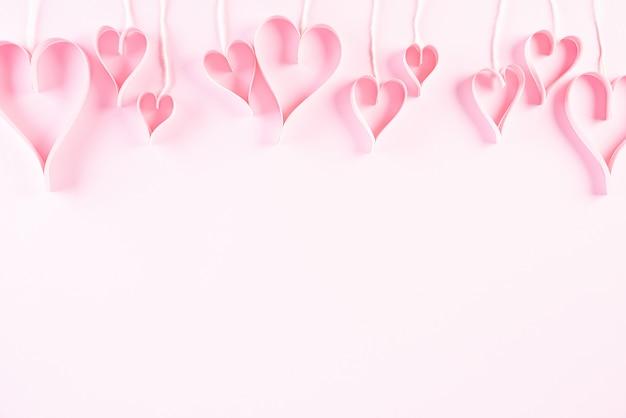 Różowe papierowe serca wisi na linach. koncepcja miłości i walentynki.