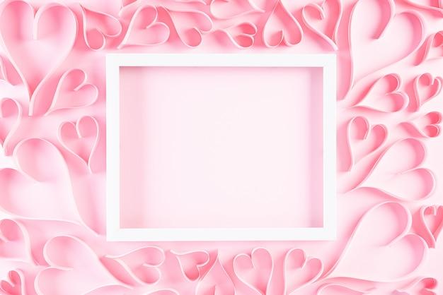 Różowe papierowe serca z białą ramką na zdjęcia. koncepcja miłości i walentynki.