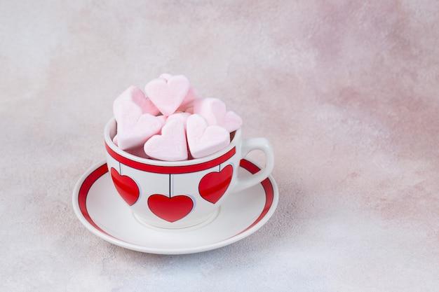 Różowe pianki w kształcie serca w filiżance