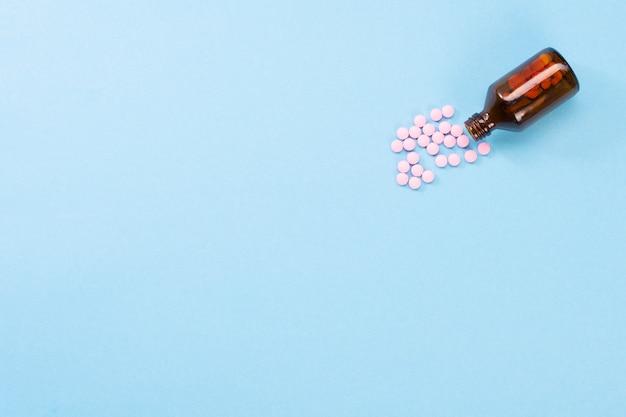 Różowe pigułki i szklana butelka. pojęcie opieki zdrowotnej i pigułki. flatlay widok z góry. niebieskie tło
