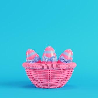 Różowe pisanki z kokardą w wiklinowym koszu na jasnym niebieskim tle w pastelowych kolorach. koncepcja minimalizmu