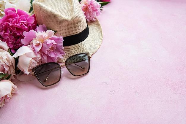 Różowe piwonie i kapelusz na różowym tle betonu