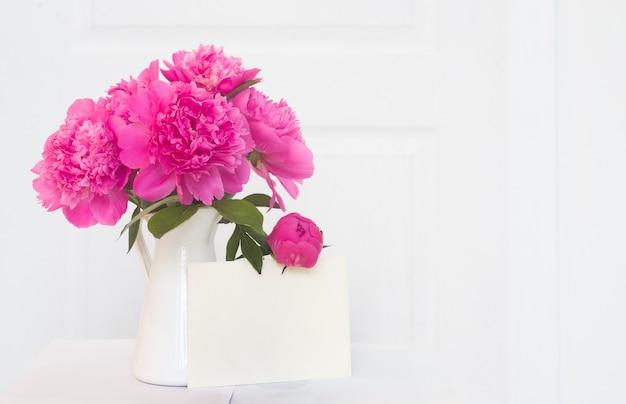 Różowe piwonie w wazonie emaliowanym na biało. piękne kwiaty w aranżacji wnętrz. biały papier na tekst zaproszenia, białe piwonie w wazonie, dekoracja wnętrz