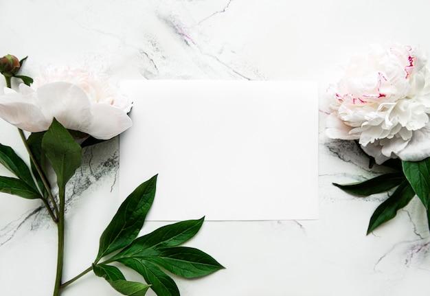 Różowe piwonie z pustą kartą na białym tle, widok z góry, miejsce na tekst. kwiatowy wzór karty z pozdrowieniami. szczęśliwych walentynek