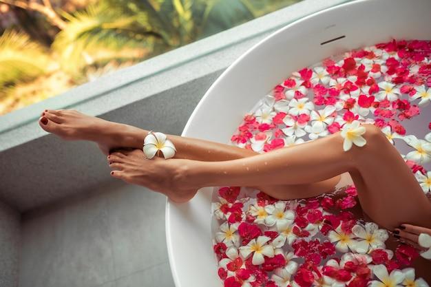 Różowe płatki róż w okrągłej wannie z nogami dziewczynki