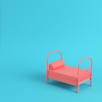 Różowe pojedyncze łóżko z poduszką na jasnoniebieskim tle