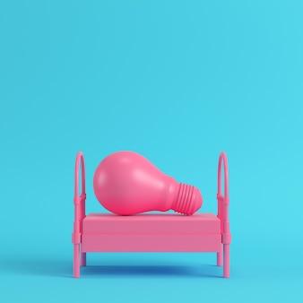 Różowe pojedyncze łóżko z żarówką na jasnoniebieskim tle