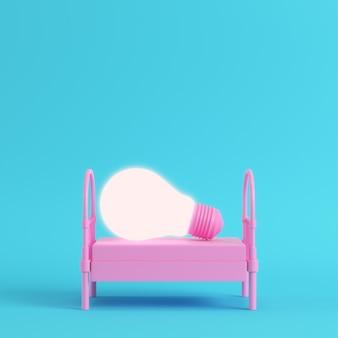 Różowe pojedyncze łóżko ze świecącą żarówką na jasnoniebieskim tle