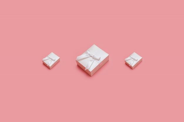 Różowe pudełka na pastelowe tło. prezentuje w stylu izometrycznym. prezent na boże narodzenie lub urodziny