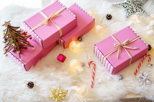 Różowe pudełka na prezenty z zamkniętą wstążką z kokardką z jasną lampą, cukierkami i gwiazdą na białym dywanie do świętowania