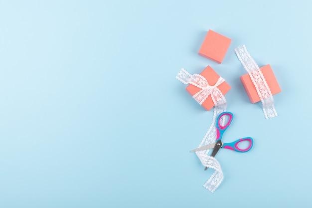 Różowe pudełka z koronką i nożyczkami