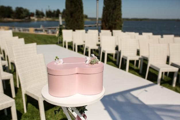 Różowe pudełko na prezenty w kształcie serca leży na stole, ślub na zewnątrz na trawniku