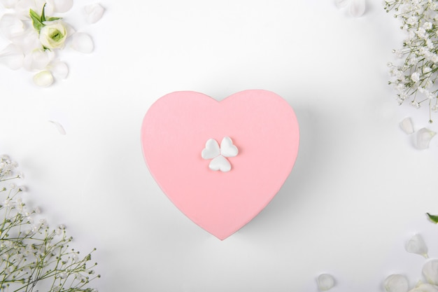Różowe pudełko w kształcie serca na białym tle z małymi witkami, celebracja walentynek