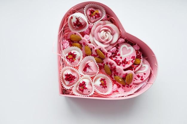Różowe pudełko w kształcie serca z ciastkami w środku posypane orzechami