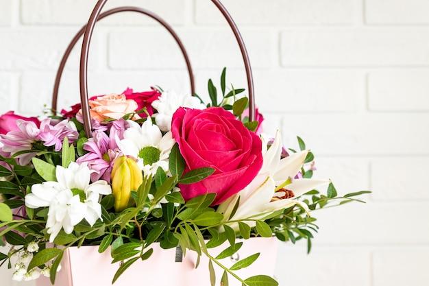 Różowe pudełko z bukietem kwiatów na stole.